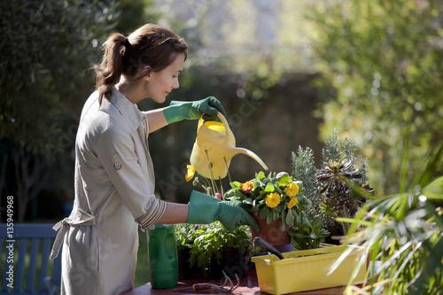 Femme qui arrose des fleurs dans un jardin stock photo for Fleurs dans un jardin