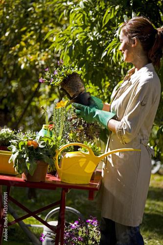 Femme souriante qui arrose des fleurs dans un jardin for Fleurs dans un jardin