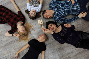 Group of different friends, adults and child, play bricks game on floor