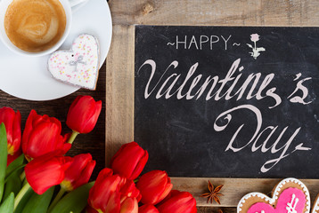 Valentines day coffee with red tulips bouquet, copy space on blackboard with happy valentines day greetings