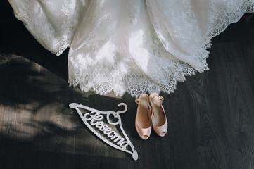 Wedding concept. bride's shoes and dress on a wooden background with sunshine light