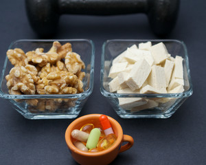 Dumbbells, tofu, nuts and dietary supplement on black background- muscle building on a vegan diet