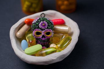 Calavera surrounded by pills in white ceramic bowls  communicating the concept that drugs can be dangerous