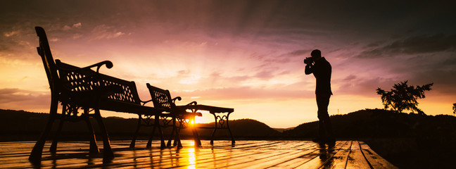 Silhouette of man with camera and red sunset.