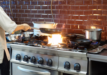 Chef is making flambe dish in restaurant kitchen