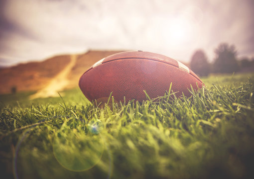 a brown american football lying on green grass in a field with a