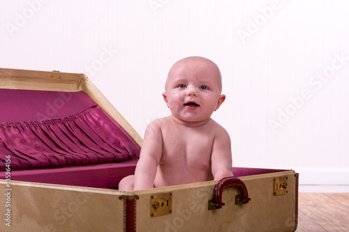 aa75d4f6e69 Adorable 6 month old baby boy sitting in a suitcase