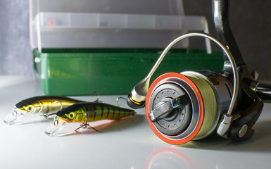 fishing reel and fishing bait on the background of the box with lures