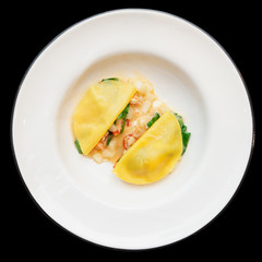 Ravioli-like dish with crayfish, apples and herbs isolated on bl