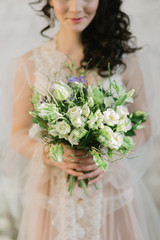 girl in boudoir dress looks at the bouquet
