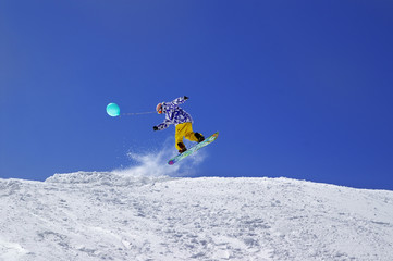 Snowboarder jump with toy balloon in terrain park at ski resort