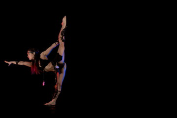 woman athlete gymnast in the form of an elf performs acrobatics on a black background in the scenic red and blue light.