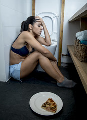 young sad and depressed bulimic woman feeling sick guilty after vomiting pizza in WC toilet