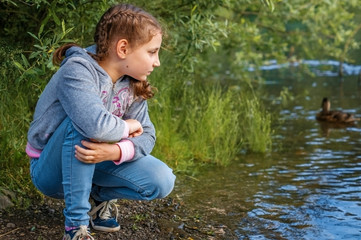 A girl child sits on the shore of a mountain lake.
