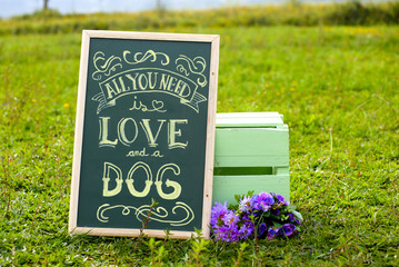 a blackboard written all you need is love and a dog on the grass