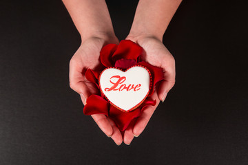 Beautiful gingerbread heart and red rose petals in the hands of the girl on a black background. Postcard for Valentine's Day, March 8, mother's Day or wedding. Free space for text