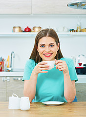 Woman smiling with teeth sitting in kitchen with coffee cup.