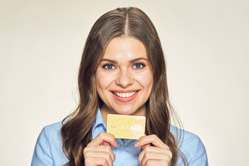 Smiling business woman holding credit gold card.