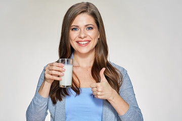 Smiling woman holding milk glass shows thumb up.