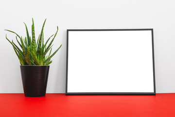 Minimalistic mock up with black frame and flower on red bookshelf or desk.