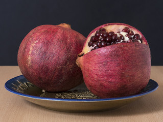 Ripe pomegranate fruit isolated on the vintage plate