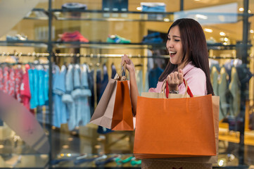 Happy young asian woman shopping in happy feeling and holding th