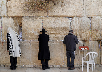 JERUSALEM - JANUARY 2017:  Jews worship at the stones of  the Western Wall, where the crevices are stuffed with notes of supplication, as seen in Jerusalem circa 2017.