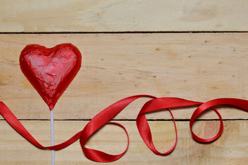 Chocolate heart wrapped in red and Red Ribbon on wood. valentine