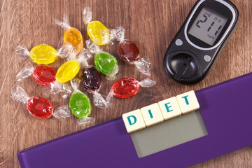 Electronic bathroom scale and glucometer with result of measurement and colorful candies, diabetes, slimming and reduction eating sweets