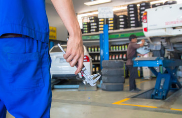 Car mechanic, Professional car mechanic changing car wheel in auto repair service.