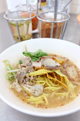 Bowl of Thai spicy noodles soup with pork and vegetables on table.