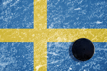 Black hockey puck on ice rink with Swedish flag.
