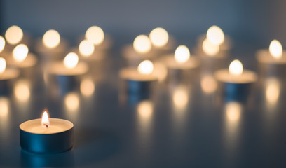 Flame of many candles burning on the background blue color Wall mural