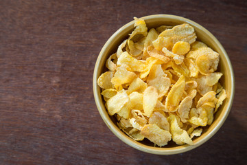 Bowl of corn flakes on wooden table.