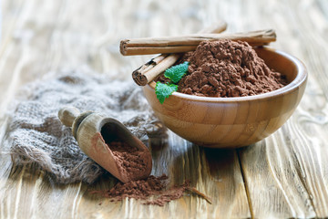 Bowl and a wooden scoop with cocoa powder.