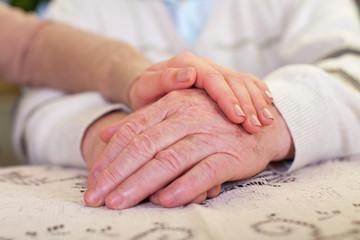Elderly hands & young carer's hands