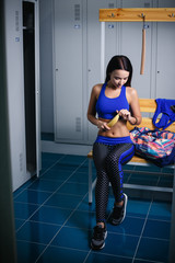 Beautiful fitness girl in cloakroom
