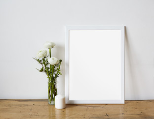 Empty frame mockup for design presentation, bouquet of flowers ranunculus and white candle on a white wall background and wooden table. Romantic minimalism design.