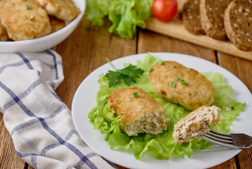 Chicken cutlets with vegetables on a wooden background
