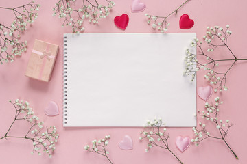 Art album, white flowers and gift box on pink background. Copy s