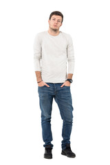 Young casual handsome man wearing jeans and sneakers with hands in pockets. Full body length portrait isolated over white studio background.