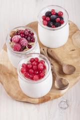 Homemade yogurt with berries in three banks