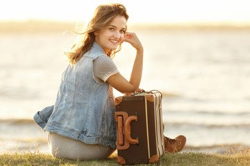 Young woman with suitcase sitting on river shore