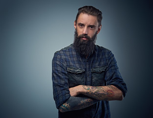 Bearded male with tattoos on his arms.