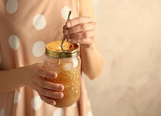 Woman holding fruit lemonade in mason jar, closeup