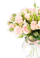 Bouquet of pink blooming fresh roses with buds in glass vase close up isolated on white background