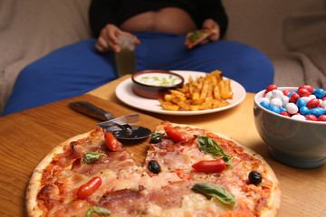 Fat man sitting on a sofa eating pizza at the table with fries, candy, sandwiches and chips. is unhealthy lifestyle  junk food.