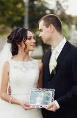 Romantic newlyweds are holding a picture in the frame