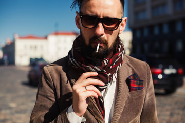 young beard  man posing in the street, cigarette