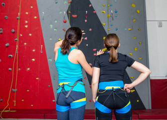 Fit Friends on the artificial climbing wall indoors discussing tactics of bouldering
